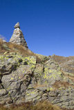 Landscape with totem of stone. Totem of stone into the blue sky in the Valle d'Aosta Royalty Free Stock Photo