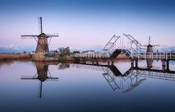 Landscape with traditional dutch windmills and drawbridge at sunrise Royalty Free Stock Photos