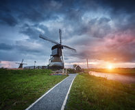 Landscape with traditional dutch windmills and path near the water canals. Royalty Free Stock Images