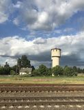 Landscape from the train window: rails, town and water tower Stock Photo