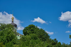 Landscape with tree and the dome of the Orthodox church. Against the blue sky with cumulus clouds stock photo