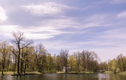 Landscape with trees and ponds under blue sky and clouds stock photo