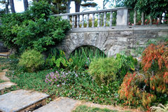 Landscape. With trees, shrubs and flowers and a stone bridge stock photos