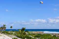 Landscape of a tropical beach with palm trees. Tourists parasailing in a blue sky. Landscape of a tropical beach with palm trees. Tourists parasailing in a blue Stock Photos