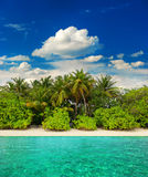 Landscape of tropical island beach. With palm trees and cloudy blue sky. view from water. travel destination Royalty Free Stock Photography