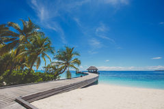 Landscape of tropical island beach with perfect sky, palms, traditional buildings Royalty Free Stock Image