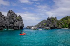 Landscape of tropical sea at sunny day. Palawan, Philippines - Apr 5, 2017. People rowing kayaks at blue lagoon in Palawan, Philippines. Palawan is one of the royalty free stock images