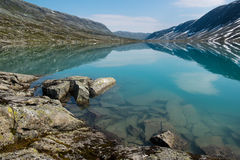 Landscape with turquoise lake, stones and mountains, Norway. Landscape with turquoise lake, stones and mountains covered by snow, Norway Royalty Free Stock Photography