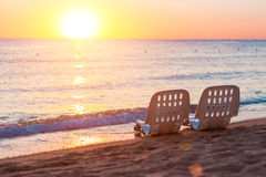 Landscape of Two Lonely beachchairs near sea and beautiful sunrise Royalty Free Stock Images