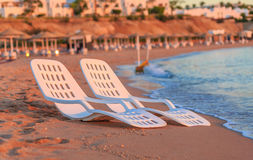 Landscape of Two Lonely beachchairs near sea and beautiful sunrise Stock Image