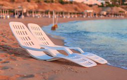 Landscape of Two Lonely beachchairs near sea and beautiful sunrise Royalty Free Stock Photo