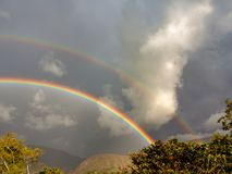 Two rainbows on a stormy sky royalty free stock photography