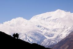 Landscape with two silhouettes with backpacks and trekking poles who are looking at shining huge mountain covered with snow and cl stock photos