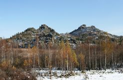 Landscape with two similar stone mountains and yellowed birches. Royalty Free Stock Photo