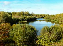 Landscape with type on lake. Autumn landscape with lake in woodland on background blue sky Royalty Free Stock Photos