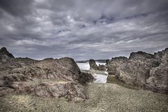 Scenic rocky beach on Pembrokeshire coast, Uk.Erosion of coastline. Landscape,UK.Cloudy sky over scenic rocky beach and puddles of sea water during low tide on royalty free stock photography