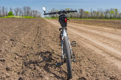 Landscape in Ukraine with an earth road between agricultural arable fields and bicycle waiting for the ride. Summer landscape in Ukraine with an earth road Stock Image