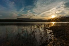Landscape of unset reflected in the lake with sunbeams. And blue cloudy sky royalty free stock image