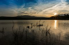 Landscape of unset reflected in the lake with sunbeams. And blue cloudy sky stock photos