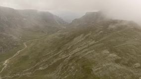 Landscape of valley between mountains. Landscape of valley between Bucegi mountains, with low, thick clouds, almost alien like landscape stock footage