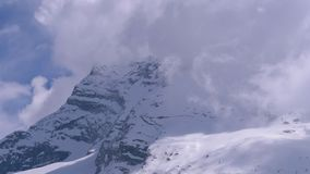 Landscape view of Alpine Mountain Snowy Peak in the Clouds. Simplon Pass. stock footage