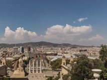 A landscape view of Barcelona, Spain. This is a sunny day with a few clouds. There is a statue watching at the city buildings direction stock photo