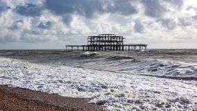 Landscape view of beach and sea with big waves. Remains of old pier in the background. Brighton, United Kingdom royalty free stock photo