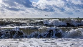 Landscape view of beach and sea with big waves. Stormy blue sky. Brighton, United Kingdom stock images