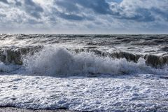 Landscape view of beach and sea with big waves. Stormy blue sky. Brighton, United Kingdom stock image