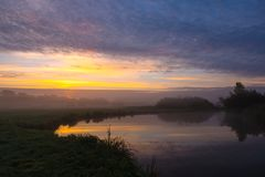 Beautiful river landscape in misty sunrise light stock images