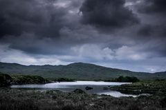 Landscape view of blue lake and dark cloudy sky above. Ireland royalty free stock image