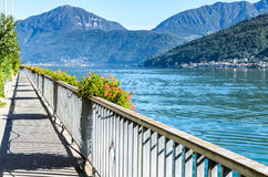 Landscape view of blue Lugano lake in summer in Morcote, Switzerland. Panoramic landscape summer view of beautiful serene blue Lugano lake under clear blue sky Royalty Free Stock Images
