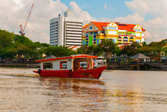 Landscape view of the city and Sarawak river. Local traditional boat for tourists. Kuching, Borneo, Malaysia Royalty Free Stock Photos