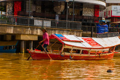 Landscape view of the city and Sarawak river. Local traditional boat for tourists. Kuching, Borneo, Malaysia Stock Photos