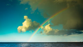 Landscape view on cloudy sky with colorful rainbow at sea or ocean outdoor. Weather. Stock Photography