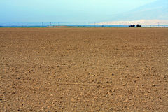 Landscape view of a dirt field and sky. Landscape view of a dirt field that has been plowed for a crop. A blue sky is in the background. Room for text/copyspace Royalty Free Stock Images