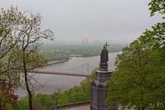 Landscape view of  Dnipro River with the Pedestrian Bridge and famous Monument  of Vladimir The Great during spring foggy morning royalty free stock photography