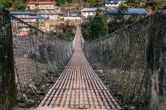 Landscape view of entrance to suspension bridge. Traditional village on the other side. Sagarmatha Everest National Park, Nepal stock photography