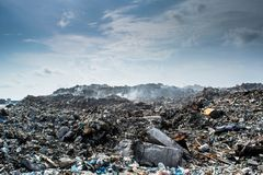 Landscape view at the garbage dump full of smoke, litter, plastic bottles,rubbish and trash at tropical island. Landscape view at the garbage dump full of smoke Royalty Free Stock Photos