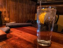 Ice water with lemon and straw on table in restaurant setting. stock photography
