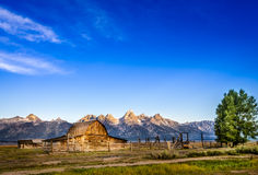Landscape view of Grand Teton mountain range and abandoned barn Royalty Free Stock Photography