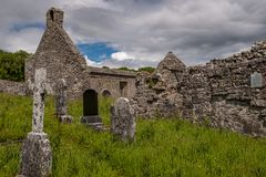 A landscape view through grave stone of the abanoned ruins of Killone Abbey that was built in 1190 and sits on the banks of the. Killone Lake, just outside royalty free stock photography