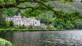 Landscape view of Kylemore Abbey and Green Victorian Walled Garden standing above blue lake. Ireland. royalty free stock photography