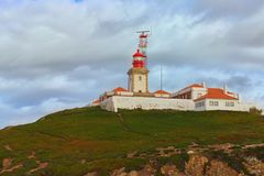 Landscape view of lighthouse on the hill at the Cabo da Roca. It is a cape which forms the westernmost extent of mainland Portugal. Scenic landscape view of stock photography