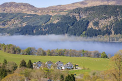 Landscape view of Loch Ness in foggy morning haze. Landscape view of Loch Ness and small village on the lake's bank in foggy morning haze. Fog over the lake stock photos