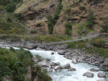 Landscape view of Long Steel Suspension bridge above the river. Nepal. Stock Photos