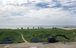 Landscape view of lush grass , abandoned earth digger sea wall , sea and sky Stock Photos
