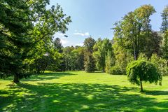Natural Park in Graz. Landscape view of natural park with path way, meadow area and green big trees among small hills and forest on bright blue sky background Royalty Free Stock Photos