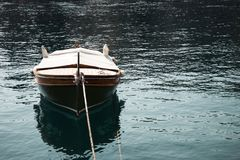 Landscape view of one brown wooden boat tied in the front. Surrounded with a blue sea with small waves reflecting sunlight. Autumn in Opatija, Croatia, Europe Stock Photos