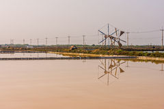 Landscape view of salt evaporation pond and wind wheel Stock Photo